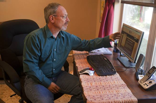 "Scott Martin, who lost his hands and feet due to the flesh eating disease, gestures to a computer screen displaying his website at his home Wednesday, Dec. 12, 2012. He wrote a passage for Chicken Soup ""Power of Positive"" and is working on a memoir."