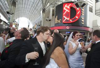 Couples celebrate with champagne at the Fremont Street Experience in downtown Las Vegas Wednesday, Dec. 12, 2012. Ryan Maluka and his bride Danielle Martinez kiss at center. Twelve couples got married at 12:12 pm at the Chapel of the Flowers as part of a KOMP 92.3 radio station promotion. The D Las Vegas put the couples up in newly upgraded rooms, hosted a reception and gave them tickets to