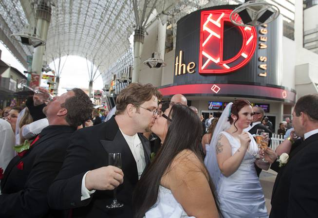 "Couples celebrate with champagne at the Fremont Street Experience in downtown Las Vegas Wednesday, Dec. 12, 2012. Ryan Maluka and his bride Danielle Martinez kiss at center. Twelve couples got married at 12:12 pm at the Chapel of the Flowers as part of a KOMP 92.3 radio station promotion. The D Las Vegas put the couples up in newly upgraded rooms, hosted a reception and gave them tickets to ""Marriage Can Be Murder,"" a comedy, murder-mystery dinner show."