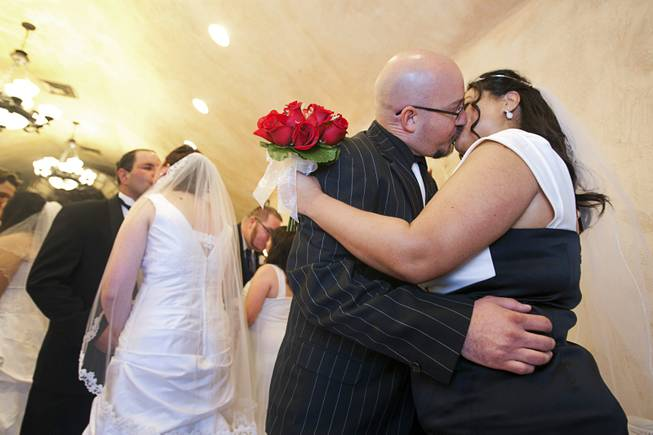 Scott Palmer and Maria St.Clair kiss after getting married in a group wedding at the Chapel of the Flowers on Las Vegas Boulevard South Wednesday, Dec. 12, 2012. Twelve couples got married at 12:12 pm at the chapel as part of a KOMP 92.3 radio station promotion. Las Vegas wedding chapels were busy all day as many couples wanted to get married on the date of 12-12-12.
