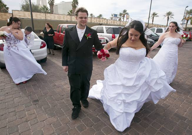 Ryan Maluka, center, his bride Danielle Martinez, and other couples prepare for photos after a group wedding at the Chapel of the Flowers on Las Vegas Boulevard South Wednesday, Dec. 12, 2012. Twelve couples got married at 12:12 pm at the chapel as part of a KOMP 92.3 radio station promotion. Las Vegas wedding chapels were busy all day as many couples wanted to get married on the date of 12-12-12.