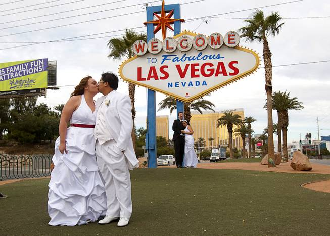 Jacqueline Plysier and Dominique Vilay of Paris, France, kiss as they pose for photos after getting married in Las Vegas on Wednesday, Dec. 12, 2012. Eric Howell and Paola Teran of Stanton, Calif., are in the background. Las Vegas wedding chapels were busy all day as many couples wanted to get married on the unique date of 12-12-12.