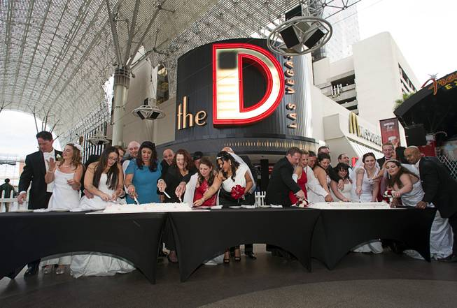 "Newlyweds cut cake in front of the D Las Vegas at the Fremont Street Experience Wednesday, Dec. 12, 2012. Twelve couples got married at 12:12 pm at the Chapel of the Flowers as part of a KOMP 92.3 radio station promotion. The D Las Vegas put the couples up in newly upgraded rooms, hosted a reception and gave them tickets to ""Marriage Can Be Murder,"" a comedy, murder-mystery dinner show."