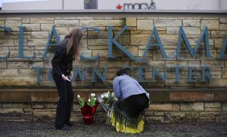 Leslie King, right and Tenille Beseda place flowers Wednesday Dec. 12, 2012, at the entrance to the scene of a multiple shooting yesterday at Clackamas Town Center Mall in Clackamas, Ore.  A gunman who opened fire on shoppers at a Portland mall had no connection to the two people he fatally shot and wanted to kill as many people as possible, police said Wednesday.