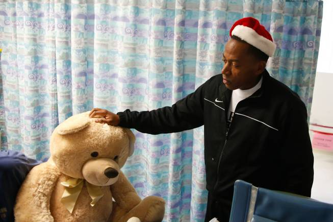 Clark County Commissioner Lawrence Weekly hands out stuffed animals to children at UMC's pediatric unit, Thursday, Dec. 13, 2012.