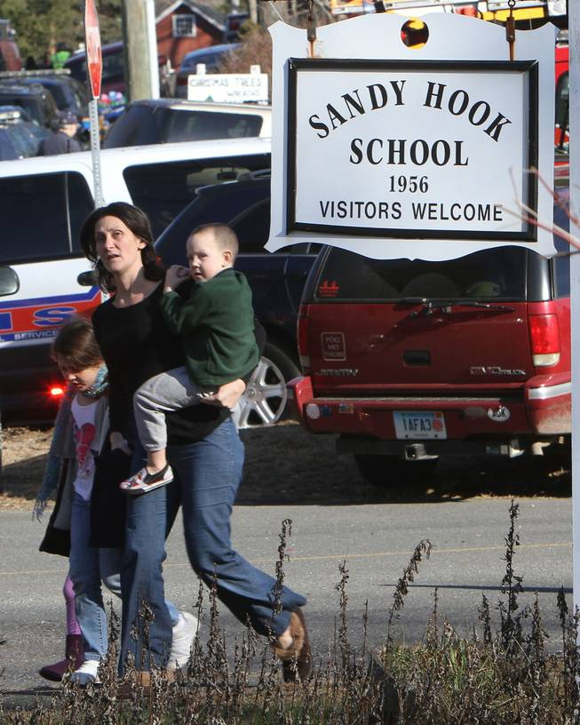 A parent walks away from the Sandy Hook Elementary School with her children following a shooting at the school in Newtown, Conn. on Friday, Dec. 14, 2012.