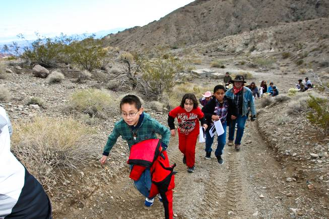 Scholarship recipient Daniel Reyes races his classmates up the trails in search of gold at the Eldorado Canyon Mine as part of the In12Days 'Ten Lords A-Leaping' celebration Saturday, December 15, 2012.