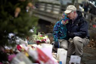 David Freedman, right, kneels with his son Zachary, 9, both of Newtown, Conn., as they visit a sidewalk memorial for the Sandy Hook Elementary School shooting victims, Sunday, Dec. 16, 2012, in Newtown, Conn.