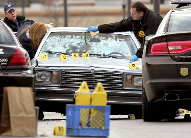 This Friday, Nov. 30, 2012, photo shows Ohio BCI agents and other law enforcement officials investigating a police shooting that killed two people in East Cleveland, Ohio. A chase that ended in 13 officers firing 137 rounds into a car, killing both people inside, began with a pop, perhaps a backfire from a car passing police headquarters or, as an officer suspected, a gunshot.