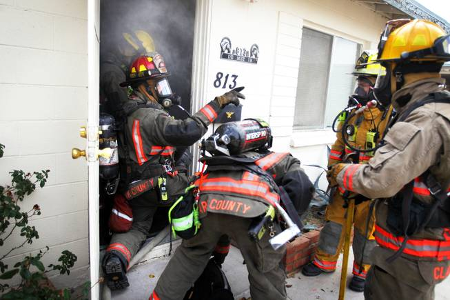 Members of Clark County Fire Department Engine 27 run a search and rescue drill at a home filled with theatrical smoke near McCarran Airport in Las Vegas on Monday, December 17, 2012.