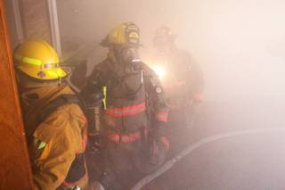 Members of Clark County Fire Department Truck 16 run a search-and-rescue drill inside a home filled with theatrical smoke near McCarran Airport on Monday, Dec. 17, 2012.