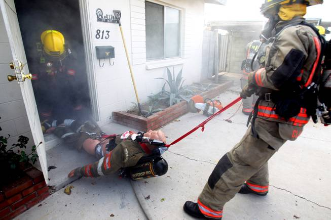Members of Clark County Fire Department Truck 16  run a search and rescue drill inside a home filled with theatrical smoke near McCarran Airport in Las Vegas on Monday, December 17, 2012.