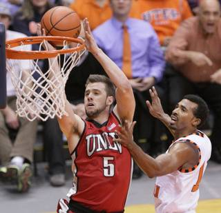 UNLV's Katin Reinhardt lays up a shot past Texas-El Paso's Jacques Streeter during a game Monday, Dec. 17, 2012, in El Paso, Texas.