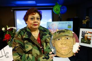 Wearing her son's military jacket, Gabriella Barajas holds a portrait of her son Army Veteran Gabriel Barajas created of sand, which will be displayed on the Donate Life's Rose Bowl parade float, during the celebration of his organ donation at the offices of the Nevada Donor Network Wednesday, December 19, 2012.