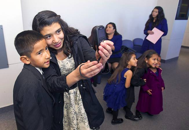 David, 9, and Vanessa Maciel, 12, take a photo as they wait outside a courtroom at family court Thursday, Dec. 20, 2012. The family officially adopted four more children for a total of eleven children.