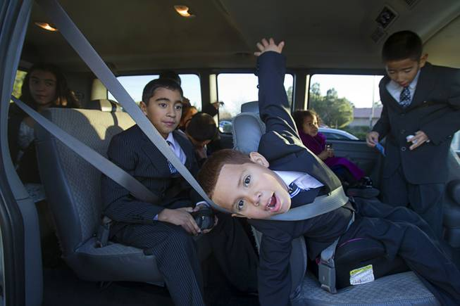 The Maciel family buckler up in their 12-passenger van after an adoption proceeding at family court Thursday, Dec. 20, 2012. The family officially adopted four more children, including Joey, 5, center, for a total of eleven children.
