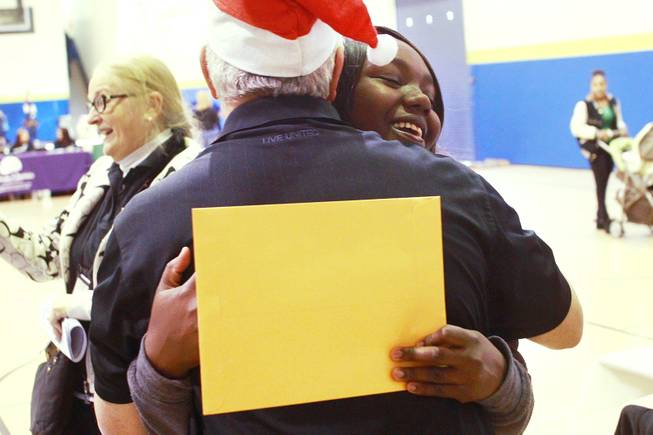 "Endia Spann hugs United Way's Ira Koplow after picking up a gift card worth $500, thanks to the largess of an anonymous ""Secret Santa"" who donated $1 million for families in southern Nevada Thursday, Dec. 20, 2012."