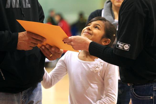 "Joanna Herrera looks up at her father Lenny Herrera as he receives a gift card worth $500, thanks to the largess of an anonymous ""Secret Santa"" who donated $1 million for families in southern Nevada Thursday, Dec. 20, 2012."