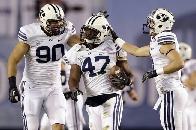 BYU linebacker Ezekiel Ansah, center, is congratulated by Bronson Kaufusi, left, and Daniel Sorensen after intercepting a San Diego State pass during the first half of the Poinsettia Bowl, Thursday, Dec. 20, 2012, in San Diego.