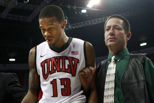 Trainer Dave Tomchek leads UNLV guard Bryce Dejean-Jones, bleeding from his ear, off the floor during their game against Canisius Saturday, Dec. 22, 2012 at the Thomas & Mack. The Runnin' Rebels won 89-74.