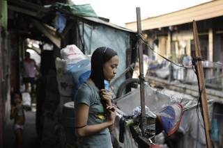 In this photo taken Dec. 4, 2012, Filipino slum dweller Jessa Balote holds her hair outside her cramped home at a place called Aroma in Tondo, Manila, Philippines. Balote, who used to tag along with her family as they collect garbage at a nearby dumpsite, is a scholar at Ballet Manila's dance program. As an apprentice, she makes around 7,000 pesos ($170) a month, sometimes double that, from stipend and performance fees.