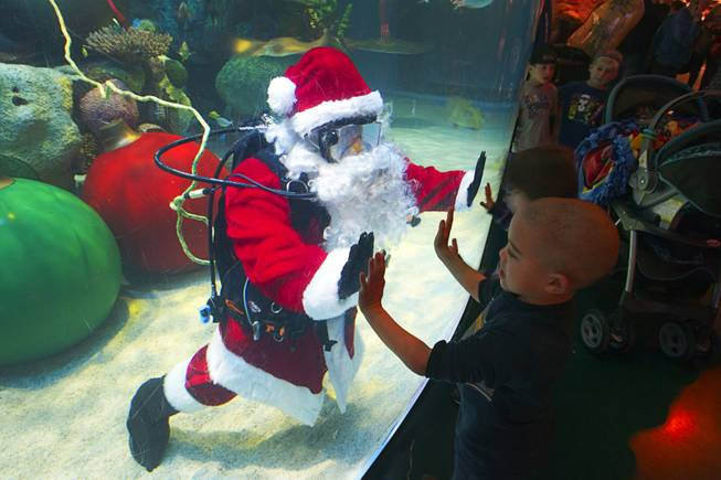 Children visit with an underwater Santa at the Silverton's  117,000-gallon aquarium Sunday, Dec. 23, 2012. Santa took Christmas present requests from children using an underwater microphone.