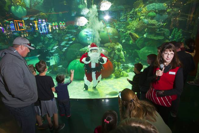 Santa waves to children from the Silverton's 117,000-gallon aquarium Sunday, Dec. 23, 2012. Santa took Christmas present requests from children using an underwater microphone.