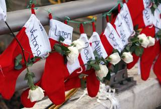 Christmas stockings with the names of shooting victims hang from railing near a makeshift memorial near the town Christmas tree in the Sandy Hook village of Newtown, Conn., Wednesday, Dec. 19, 2012.