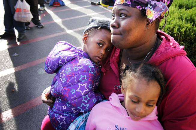 Evelyn (who lives at Shade Tree Shelter and did not want her and her daughters last names used) waits in line with her daughters Jazmine, left, 2, and Pasha-e, 5, during a Christmas Day event to feed and clothe the homeless and needy organized by the nonprofit organization Broken Chains in Las Vegas on Tuesday, December 25, 2012.