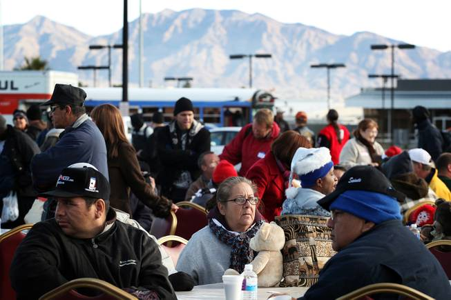 People gather at tables to dine during a Christmas Day event to feed and clothe the homeless and needy organized by the nonprofit organization Broken Chains in Las Vegas on Tuesday, December 25, 2012.
