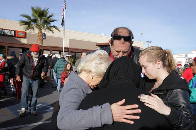 Shelly Alfaro, from left, prays with her husband David Alfaro and daughter Chelsea Alfaro, 18, during a Christmas Day event to feed and clothe the homeless and needy organized by the nonprofit organization Broken Chains in Las Vegas on Tuesday, December 25, 2012.