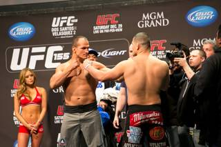 Junior dos Santos and Cain Velasquez face off during the weigh-in for UFC 155, Friday, Dec. 28, 2012.