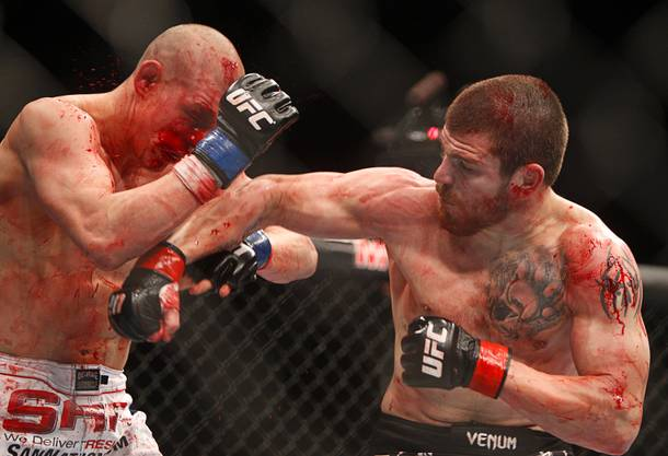 Jim Miller , right, of Whippany, N.J. connects on Joe Lauzon of Bridgewater, Mass. in a lightweight bout during UFC155 at the MGM Grand Garden Arena Saturday, Dec. 29, 2012. Miller defeated Lauzon by unanimous decision.