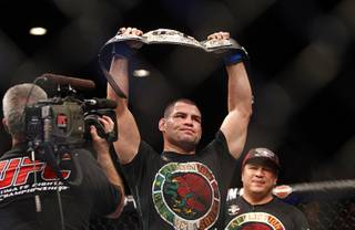 Cain Velasquez holds up the championship belt after defeating Junior Dos Santos during a heavyweight title bout UFC155 at the MGM Grand Garden Arena Saturday, Dec. 29, 2012. Velasquez reclaimed the belt by unanimous decision.