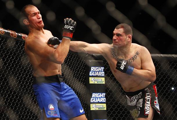 Cain Velasquez, right, connects with a punch that staggers heavyweight champion Junior Dos Santos during the first round of their heavyweight title bout UFC155 at the MGM Grand Garden Arena Saturday, Dec. 29, 2012. Velasquez took back the title by unanimous decision.