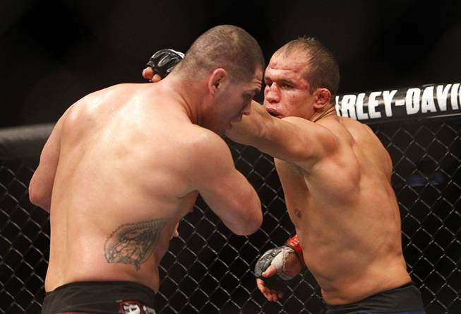Heavyweight champion Junior Dos Santos, right, punches at  Cain Velasquez during a heavyweight title bout UFC155 at the MGM Grand Garden Arena Saturday, Dec. 29, 2012. Velasquez reclaimed the belt by unanimous decision.
