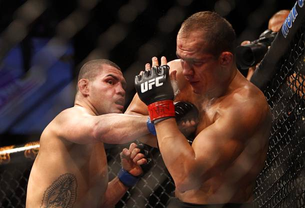 Cain Velasquez, left, punches heavyweight champion Junior Dos Santos during a heavyweight title bout UFC155 at the MGM Grand Garden Arena Saturday, Dec. 29, 2012. Velasquez reclaimed the belt by unanimous decision.