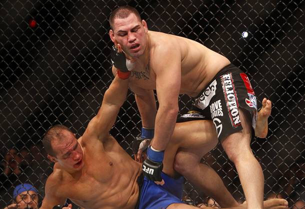 Heavyweight champion Junior Dos Santos, left, tries to push away Cain Velasquez during a heavyweight title bout UFC155 at the MGM Grand Garden Arena Saturday, Dec. 29, 2012. Velasquez reclaimed the belt by unanimous decision.