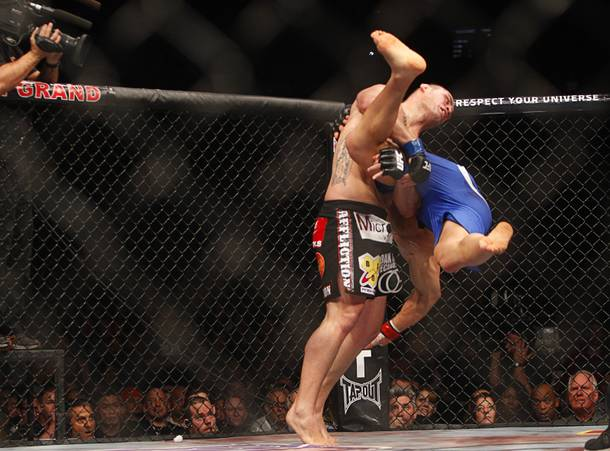 Cain Velasquez, left, throws down heavyweight champion Junior Dos Santos during a heavyweight title bout UFC155 at the MGM Grand Garden Arena Saturday, Dec. 29, 2012. Velasquez reclaimed the belt by unanimous decision.
