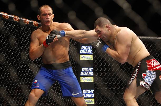 Cain Velasquez, right, punches heavyweight champion Junior Dos Santos during a heavyweight title bout UFC155 at the MGM Grand Garden Arena Saturday, Dec. 29, 2012. Velasquez reclaimed the belt by unanimous decision.
