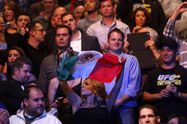 A woman waves a Mexican flag at the start of the fight between Cain Velasquez and heavyweight champion Junior Dos Santos during UFC155 at the MGM Grand Garden Arena Saturday, Dec. 29, 2012. Velasquez reclaimed the belt by unanimous decision.