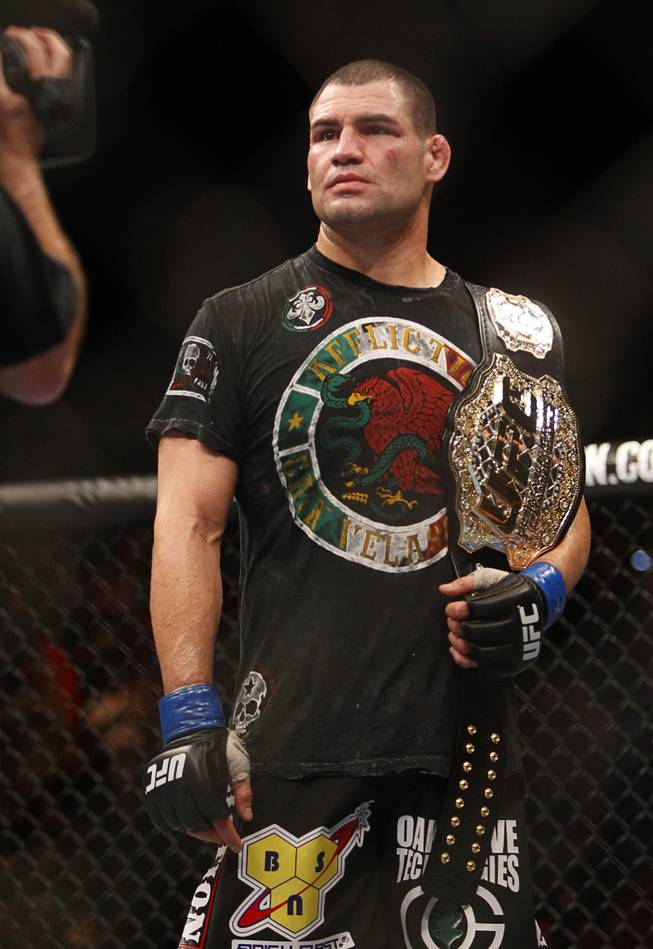 Cain Velasquez holds the championship belt after defeating Junior Dos Santos during a heavyweight title bout UFC155 at the MGM Grand Garden Arena Saturday, Dec. 29, 2012. Velasquez reclaimed the belt by unanimous decision.