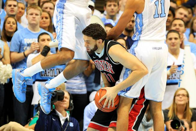 UNLV forward Carlos Lopez-Sosa is fouled by North Carolina forwards J.P. Tokoto, left, and Brice Johnson during their game Saturday, Dec. 29, 2012 at the Dean Smith Center in Chapel Hill, N.C.