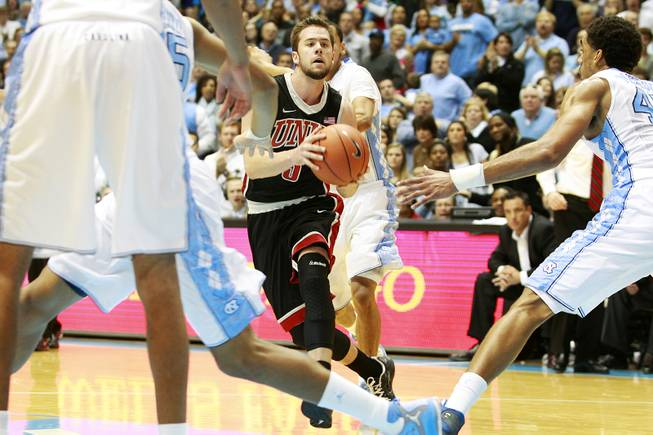 Surrounded by North Carolina players, UNLV guard Katin Reinhardt looks for an open teammate during their game Saturday, Dec. 29, 2012 at the Dean Smith Center in Chapel Hill, N.C. North Carolina won the game 79-73.