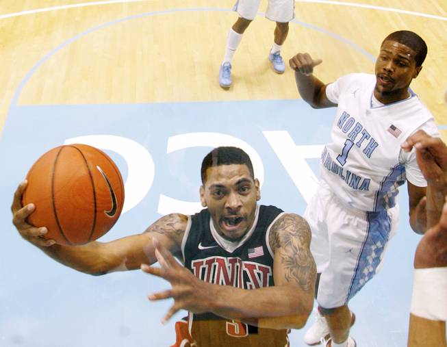 UNLV guard Anthony Marshall drives to the basket past North Carolina guard Dexter Strickland during their game Saturday, Dec. 29, 2012 at the Dean Smith Center in Chapel Hill, N.C. North Carolina won the game 79-73.