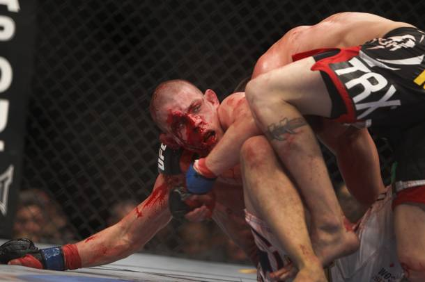 Joe Lauzon, left, of Bridgewater, Mass. bleeds from cuts on his face as he fights Jim Miller of Whippany, N.J.during a lightweight bout UFC155 at the MGM Grand Garden Arena Saturday, Dec. 29, 2012.