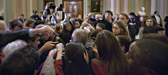 "Reporters surround Assistant Majority Leader Sen. Richard Durbin, D-Ill., outside the Senate chamber during negotiations on the ""fiscal cliff"" at the Capitol in Washington, Sunday, Dec. 30, 2012."