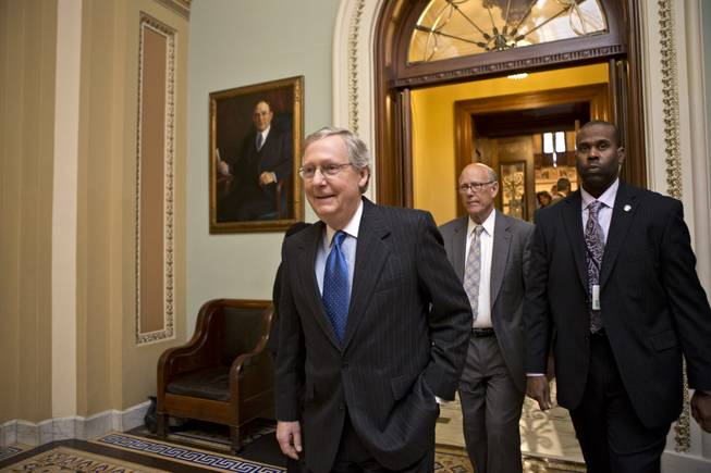 "Senate Minority Leader Mitch McConnell, R-Ky., followed by Sen. Pat Roberts, R-Kan., second from right, leaves the Senate chamber to meet with fellow Republicans in a closed-door session as the ""fiscal cliff"" negotiations continue at the Capitol in Washington, Sunday, Dec. 30, 2012."