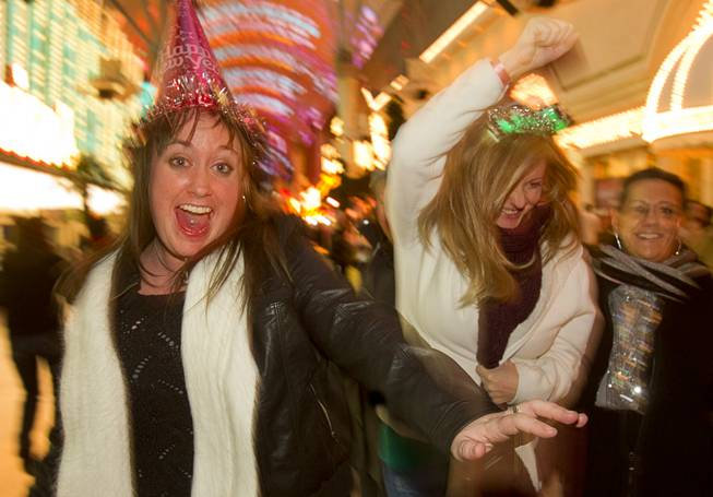 Ashley Smith, left, and Erica Forsstrom of Las Vegas dance during the New Years Eve party at the Fremont Street Experience Monday, Dec. 31, 2012.