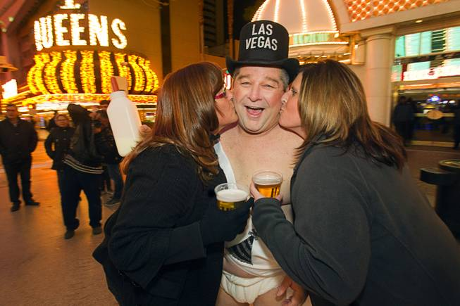"""Tank"" Campbell of North Carolina gets kisses from Cheryl Strassman, left, and Becky Vanheubel of Appleton, Wis. during the New Years Eve party at the Fremont Street Experience Monday, Dec. 31, 2012. Campbell, a truck driver who is on a layover in Las Vegas, said it was his first time to work as a street performer."